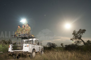 Night-time listening posts like this one on a hill in the south of the reserve are critical to their mission, visual policing and early detaction.  Collette Ngobeni holds the spotlight bythe light of the full moon. The ladies of the first all female Anti-Poaching Unit in Africa, on patrol, making roadblocks and sitting in listening posts at night in Balule Private Nature Reserve.