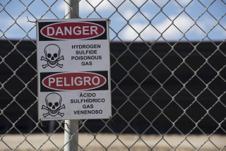 """At a fracturing waste processing site near Aztec New Mexico a sign warns of Hydrogen Sulfide Gas, which can cause immediate death if inhaled.  Hydraulic fracturing has created America's energy boom, but it has also created major environmental problems that are only now being fully researched and understood. Throughout the country """"fracking"""" has local communities up in arms over highly dangerous airborn pollutants, and reasearchers from NASA, The National Oceanic and Atmospheric Assosciation (NOAA) and the University of Colorado are confirming that massive amounts of Methane and other Volatile Organic Compounds (VOCs) are being released at levels between 2 and 5 times higher than Environmental Protection Agency estimates."""