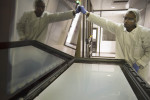 Luando Mkosi works on the system that deposits the patented surface that generates electricity onto the glass panels.  Dr. Vivian Alberts and his team have created the first wholly African designed and built solar panels at their facility in Stellenbosch South Africa. The panels are cheaper, generate more power in low light and can handle higher temperatures than their traiditional silicone cousins.